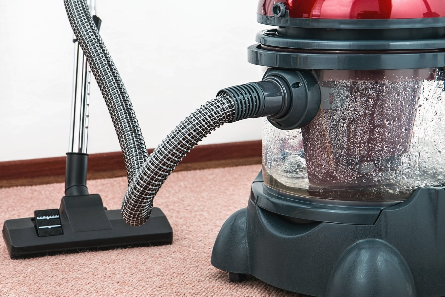Small red vacuum clear canister filled with water with hose and floor sweeper